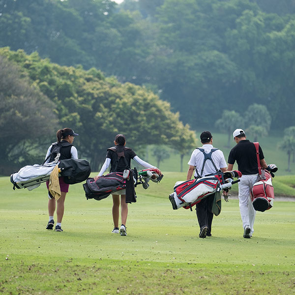 men with golf bags on course